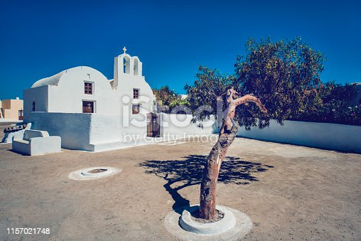 Bougainvillea Tree In Front Of Traditional Church In Santorini, Greece