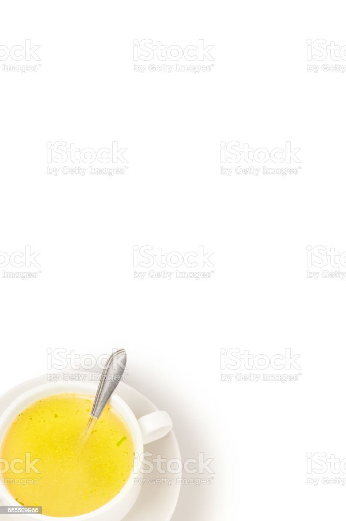 Bouillon and greens in bowl on white background. stock photo