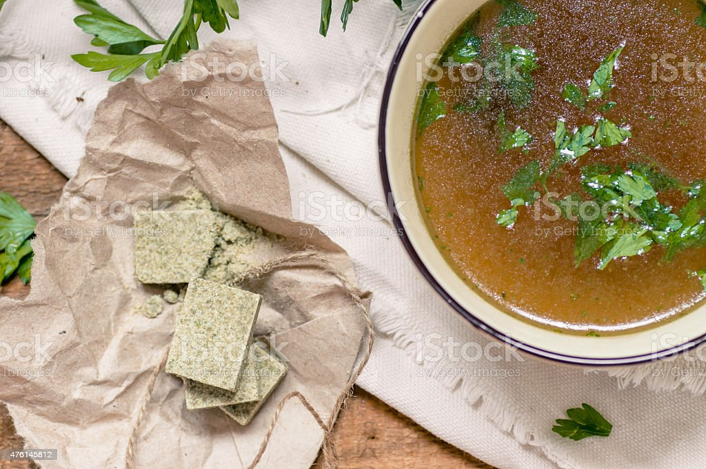 Bouillon cubes next to a bowl of broth stock photo