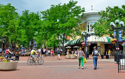 Boulder, Colorado, USA - June 16, 2013: Typical street scene with a variety of people in the shopping district of Boulder with colorful and quaint shops and restaurants.