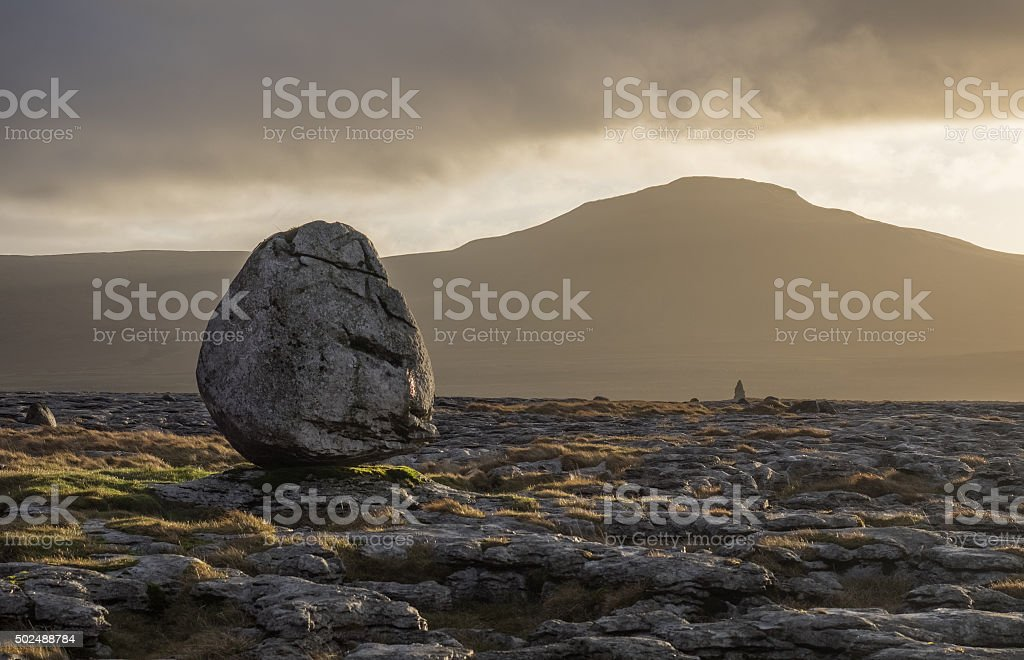 Boulder on Twistleton Scar, Yorkshire Dales, sunrise behinda stock photo
