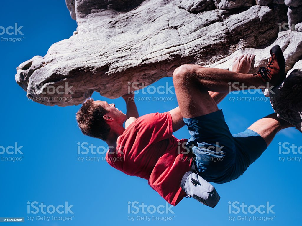 Bouldering rock climber hanging beneath extreme overhang against blue sky stock photo
