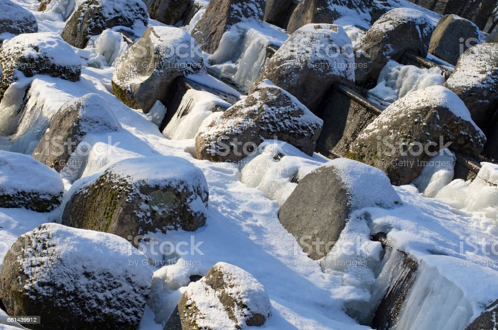 Boulders covered with snow in the cascade diagonally stock photo