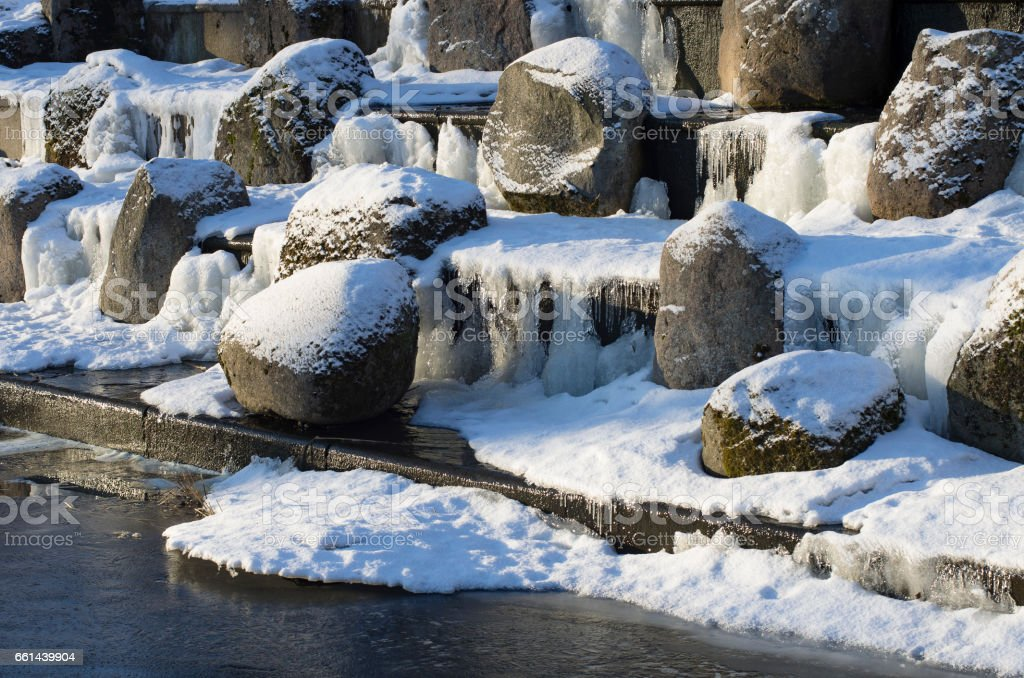 Boulders covered with snow in the cascade in the thaw stock photo