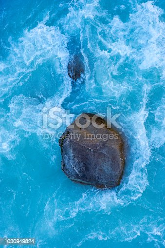 Looking down onto great rocks and boulders caught in the fast flowing and alluvial-blue waters of the Hooker River, in the Mt Cook National Park