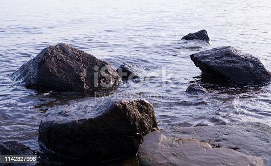 wet boulders in the water. nature, geologic.