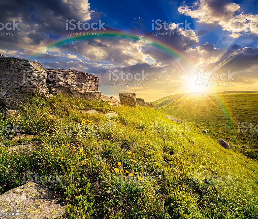 boulders on hillside in high mountains at sunset stock photo