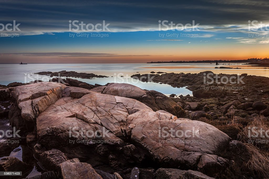 Boulders On The Shore At Sunset With Lighthouse In The Distance stock photo