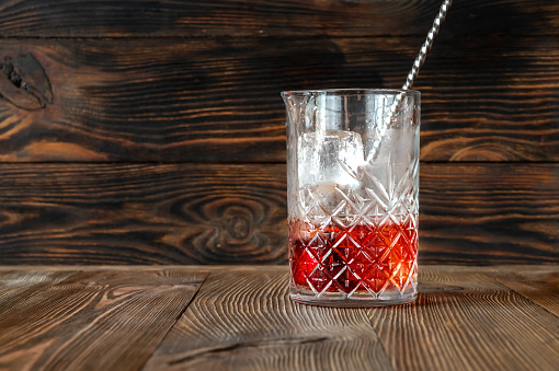 Glass of Boulevardier cocktail in mixing glass