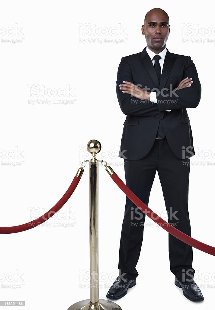 Bouncer in suit standing behind crowd control post against white royalty-free stock photo