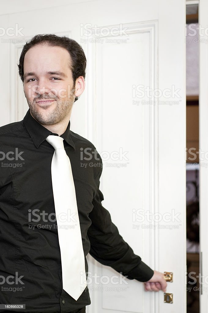 Bouncer wearing tie and shirt opening door royalty-free stock photo