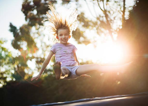 auf und ab springen auf dem trampolin - gartentrampolin stock-fotos und bilder