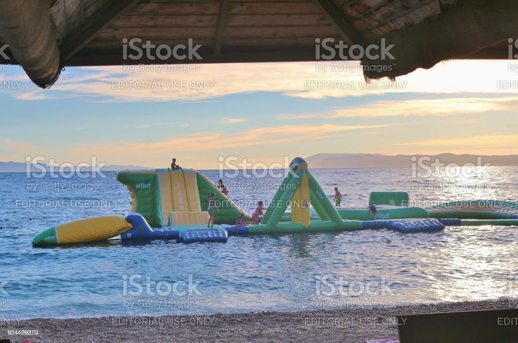 Bouncy castle in the sea, seen from a seaside cafe. On the beach of Tucepi near Makarska, Croatia. stock photo