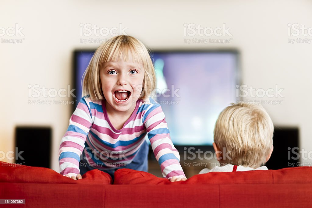 Bouncy little girl jumps excitedly on the couch stock photo