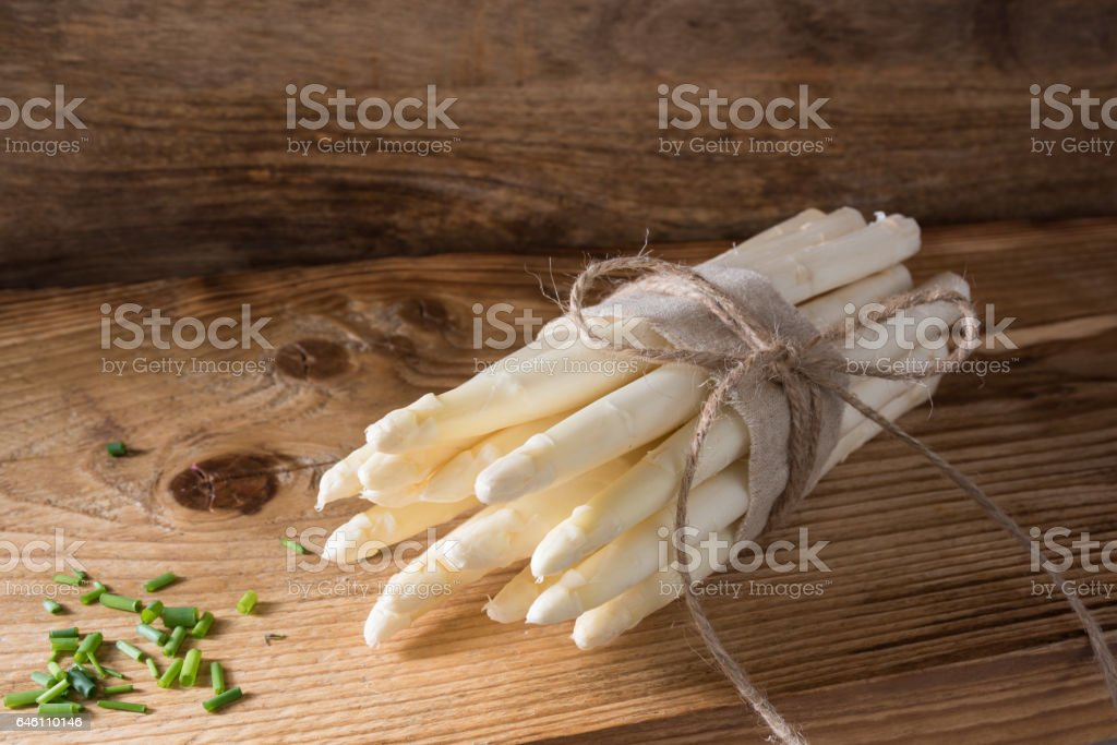Bound asparagus on a wooden board stock photo