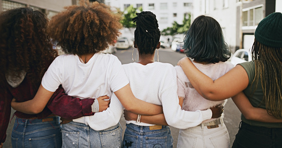 Rearview shot of a group of unrecognizable young friends walking with their arms around each other in the city