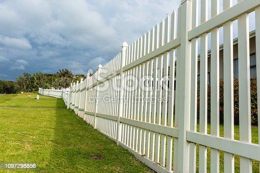 White boundary vertical slat plastic pvc fence wall along roadside grass landscape.