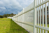 White boundary vertical slat plastic pvc fence wall along roadside grass landscape.
