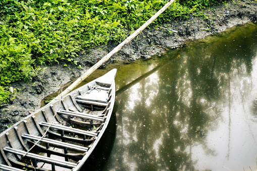 A bounded wooden boat with a laying bamboo on a pond