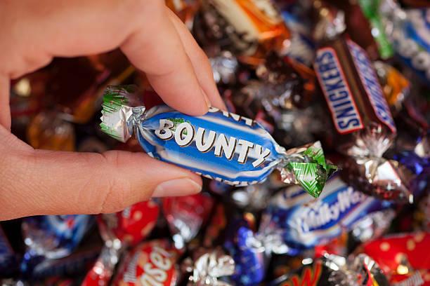 bounty süßigkeit in woman's hand - milky way stock-fotos und bilder