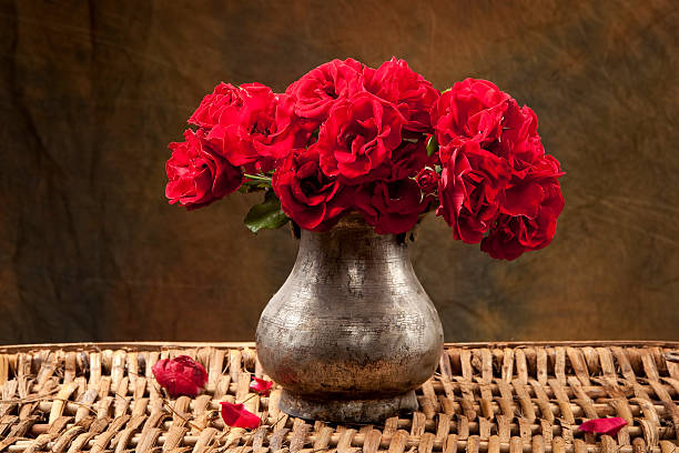 bouqet of red roses on rattan basket with grunge background - silberne vase stock-fotos und bilder