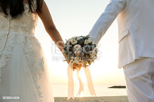 Two couple have bouquet at the sunset beach