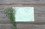 istock Bouquet flower grass and wrinkled green paper on a brown wooden background. 690224296