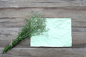 istock Bouquet flower grass and wrinkled green paper on a brown wooden background. 694719480