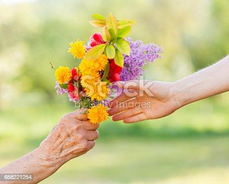 istock Bouquet flowers in hands 658221254