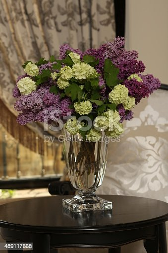 istock Bouquet from branches of lilac in transparent vase on black 489117668