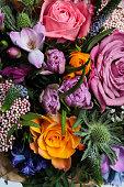 Multicolored bouquet of Eringium, Ozotamus, Rosa and other flowers