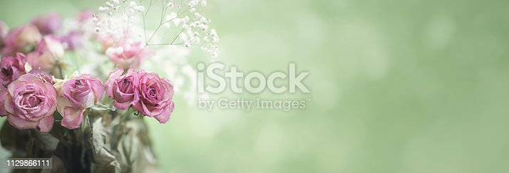 istock Bouquet of aged red rose border or banner with copy space 1129866111