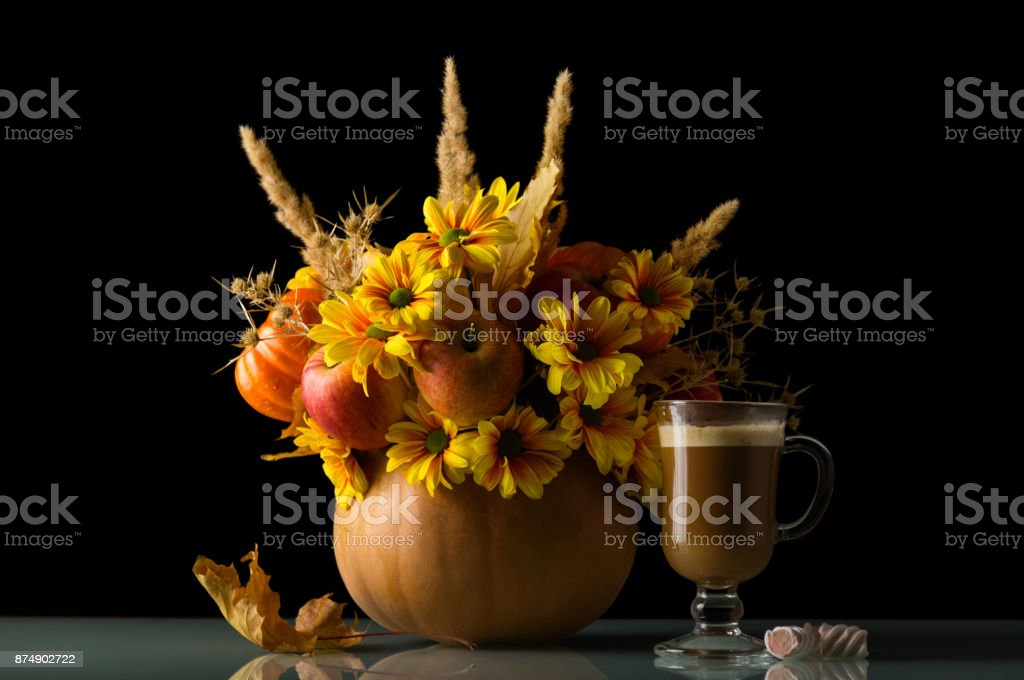 A bouquet of apples and flowers in a pumpkin, glass of cappuccino and sweets, isolated on black stock photo
