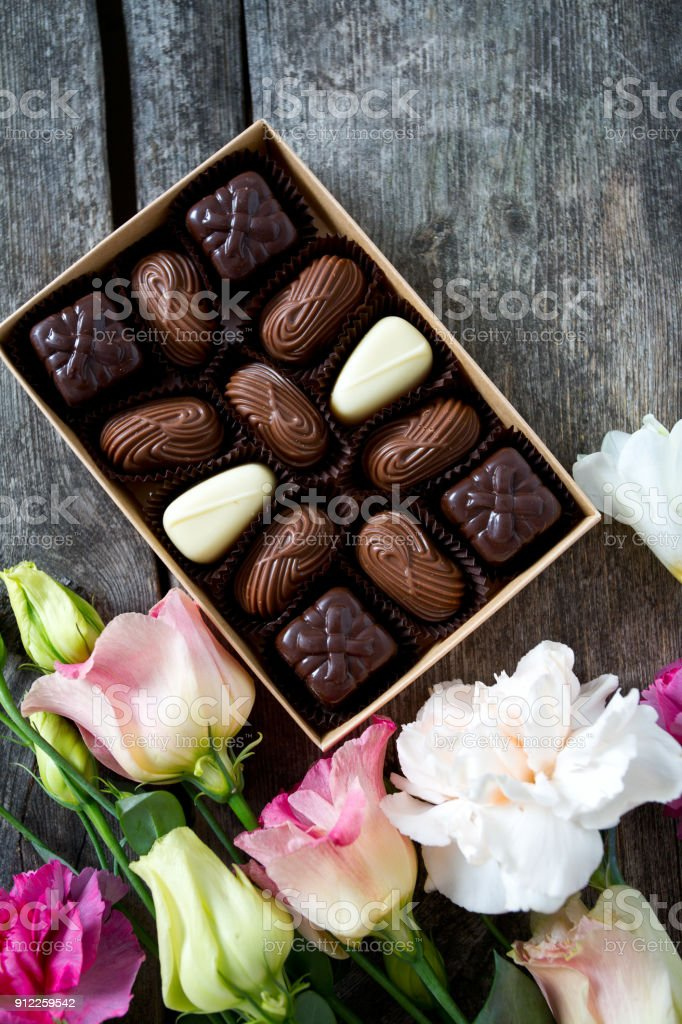 Bouquet Of Beautiful Flowers And Chocolate Box On Wooden Surface