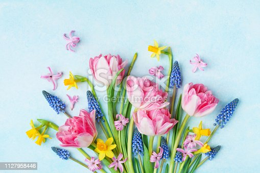 istock Bouquet of beautiful spring flowers on pastel blue table top view. Greeting card for International Women Day. 1127958446