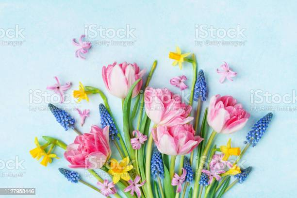 Photo of Bouquet of beautiful spring flowers on pastel blue table top view. Greeting card for International Women Day.