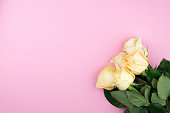 istock Bouquet of beige roses on pink background, flat lay, top view, copy space. Mothers day. Valentines day 674487094
