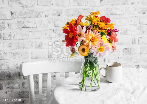 istock Bouquet of bright colorful autumn flowers on a bright table in a cozy light kitchen. Copy space, flat lay 1171178718