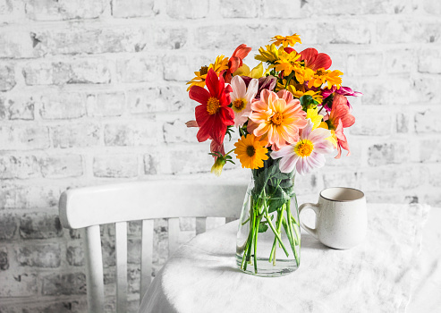 Bouquet of bright colorful autumn flowers on a bright table in a cozy light kitchen. Copy space, flat lay