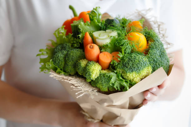 Bouquet of broccoli, celery, carrots, paprika and lettuce in the hands of a woman stock photo
