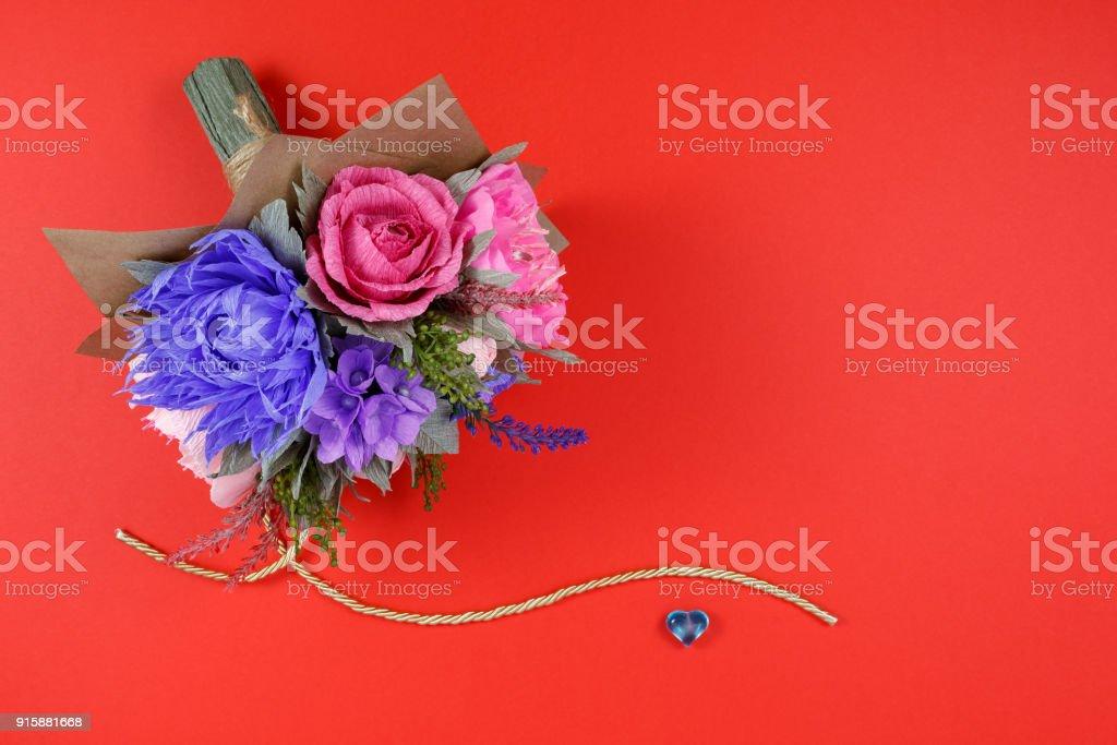 Un Bouquet De Fleurs En Papier Colore Et Un Petit Coeur Bleu Sur