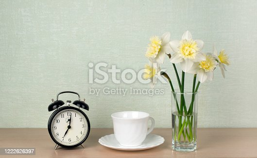 905623256 istock photo A bouquet of daffodils, a cup of tea or coffee, a mechanical alarm clock on a turquoise background. Morning breakfast 1222626397