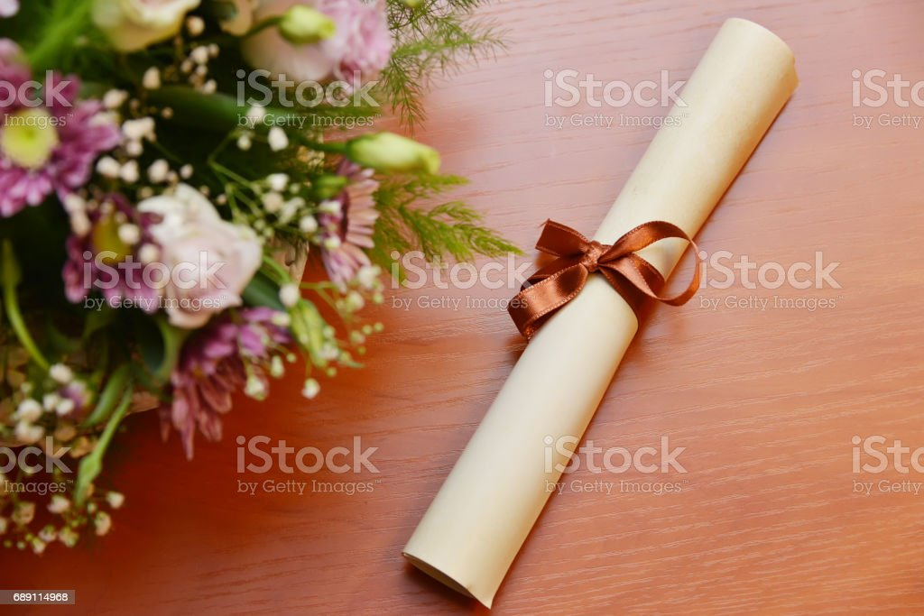 Bouquet of different flowers and rolled parchment with ribbon.