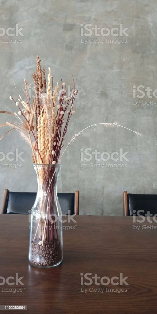 Bouquet of dried flowers in the vase that\'s on the wooden table.