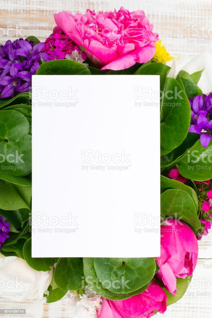 bouquet of flowers and a blank sheet of paper on wooden planks royalty-free stock photo