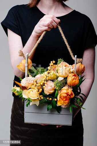 Bouquet of flowers in a wooden box in the hands of a woman florist. Rosa spray Catalina, ilex, skimmia, carnation, eustoma, tulip