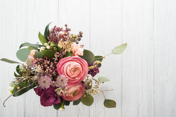 Bouquet de fleurs dans la tasse d'étain sur le fond clair - Photo