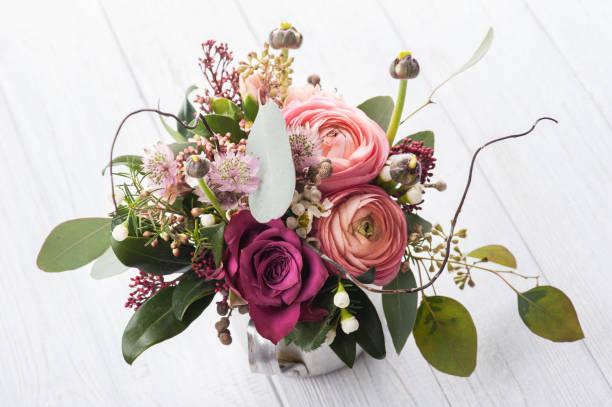 Bouquet de fleurs dans une tasse étain sur fond clair - Photo