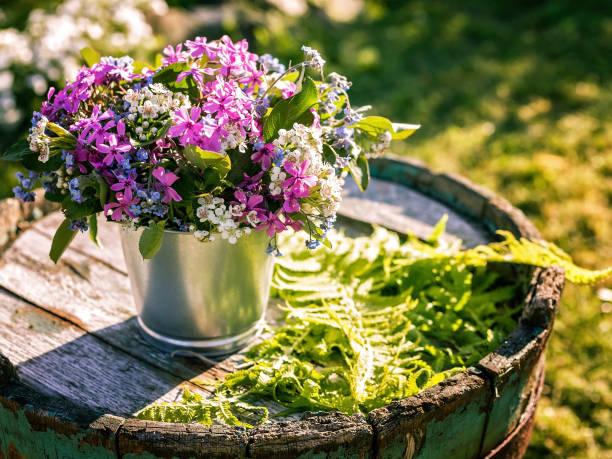blumenstrauß in zinntöpfen auf einem alten holzfass. hochzeit outdoor floristik - zinn hochzeit stock-fotos und bilder