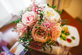 bouquet of beautiful flowers with roses in a small vase in vintage style on the table
